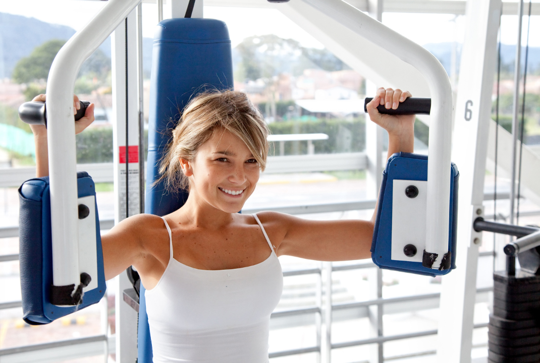 Woman at the gym doing arms exercises on a machine