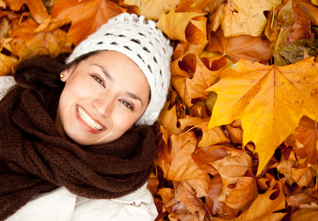 Portrait of an autumn woman lying over leaves and smiling