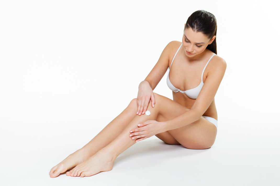 Young woman applying moisturizer on legs
