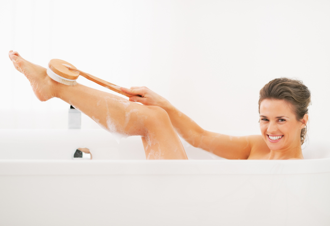 Happy young woman washing with body brush in bathtub